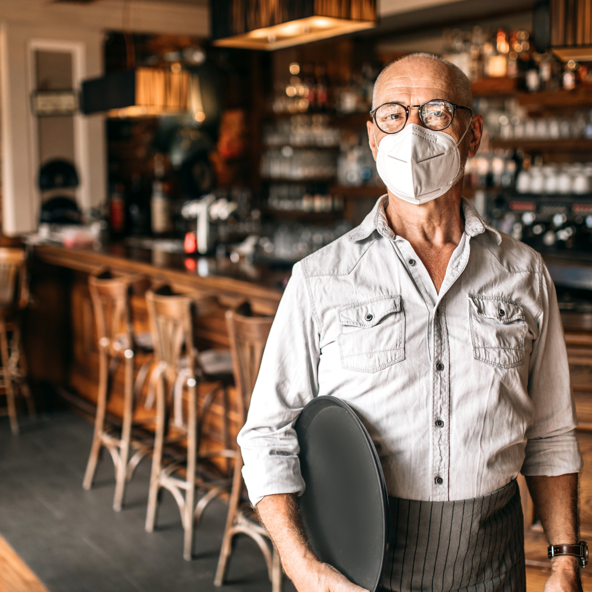 older bar man standing in front of his bar holding a server tray